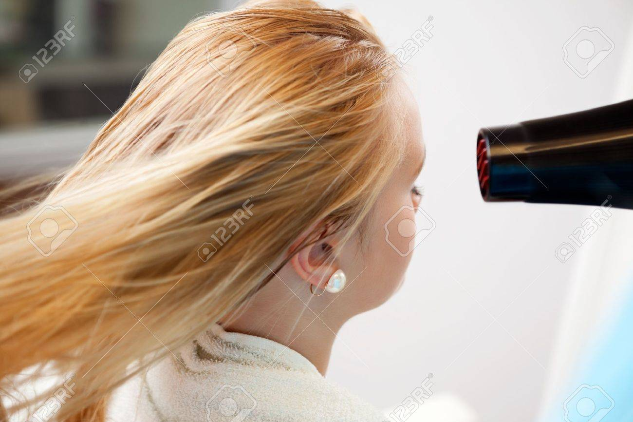 Blond hair of a young woman being dried by blow dryer at parlor Stock Photo - 14454667