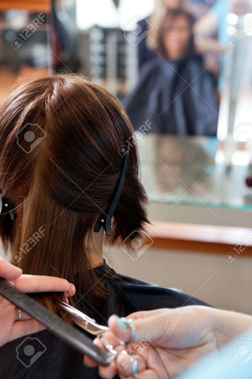 Close up of hairdresser giving a haircut to female customer at parlor Stock Photo - 14508255