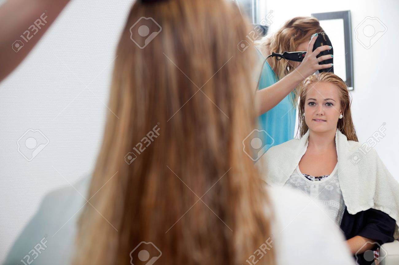 Mirror reflection of beautician drying long blond hair with hair dryer at parlor Stock Photo - 14508116