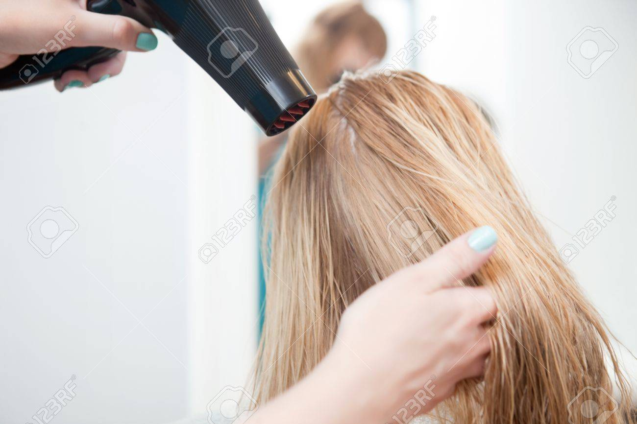 Stylist drying womans hair in beauty salon Stock Photo - 14508106