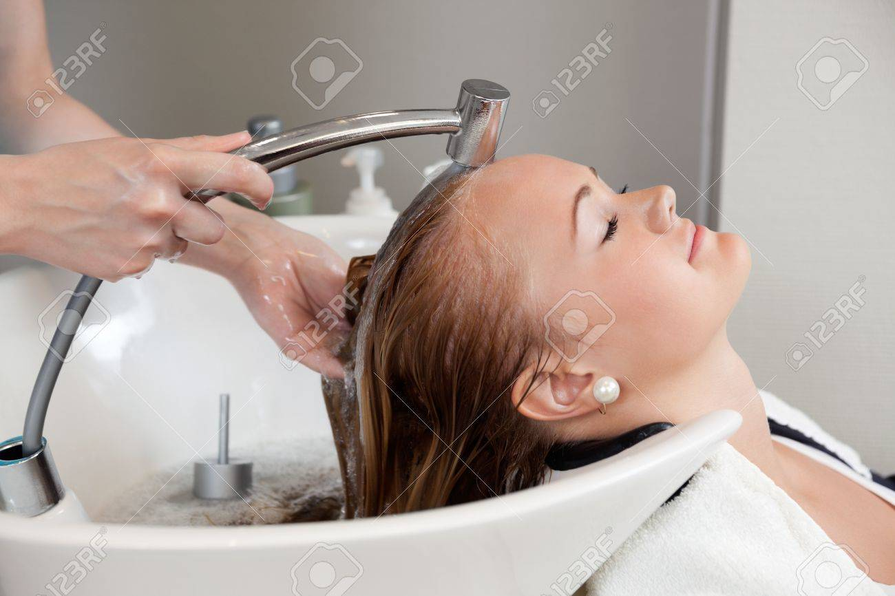 Side view of a beautiful young woman getting a hair washed by hairdresser at salon Stock Photo - 14508118