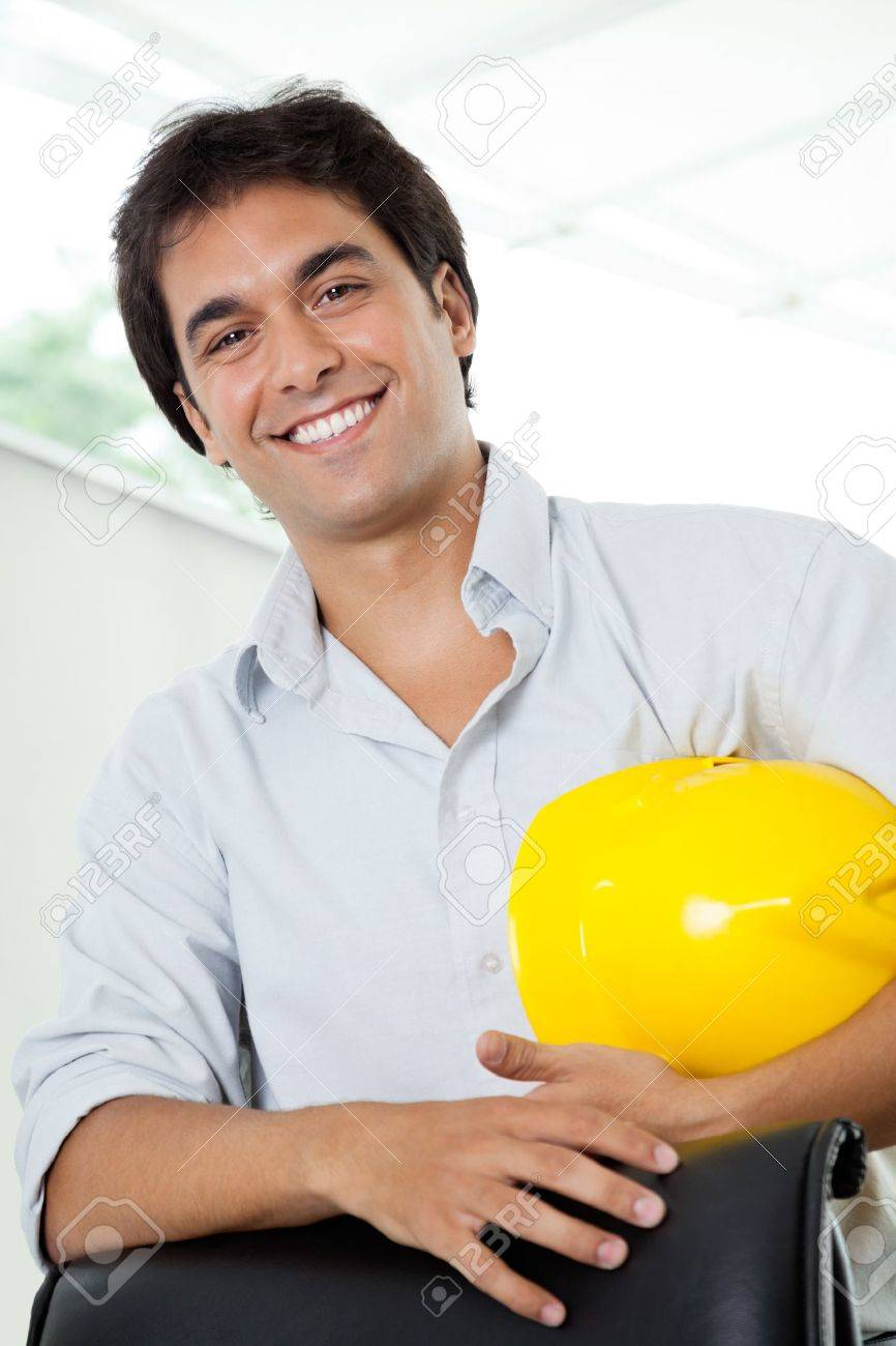 Portrait of happy young male architect holding yellow hardhat while standing by office chair Stock Photo - 14838504