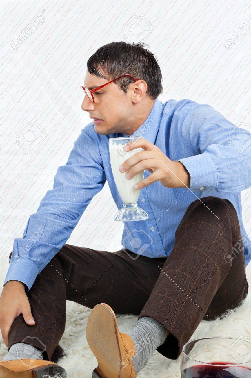 Young male geek making a face while holding glass healthy drink Stock Photo - 15190692