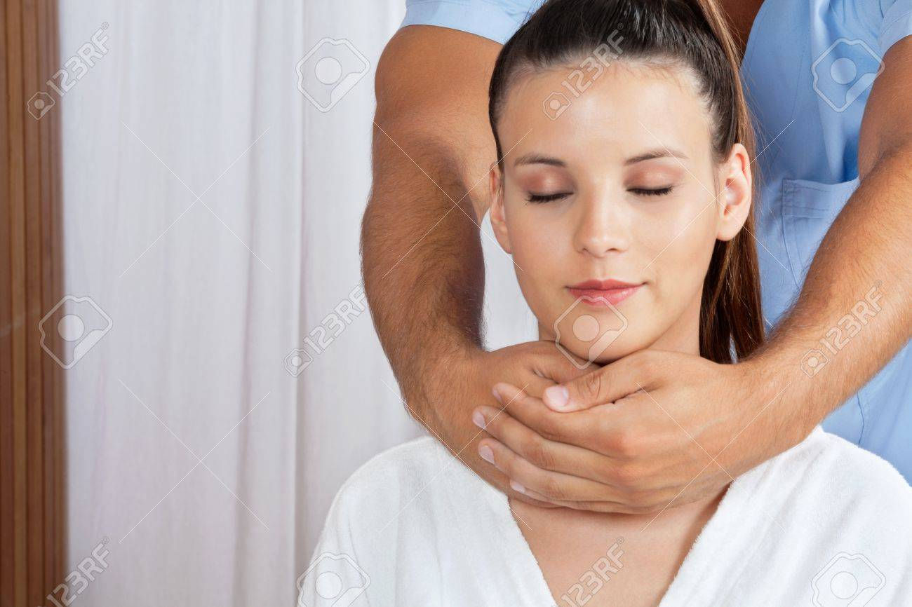 Relaxed young female with eyes closed receiving neck massage by male masseuse Stock Photo - 15190877
