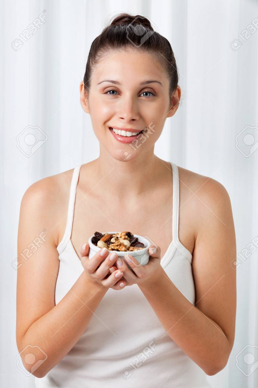Portrait of an attractive young woman holding bowl of dry fruits Stock Photo - 15205306