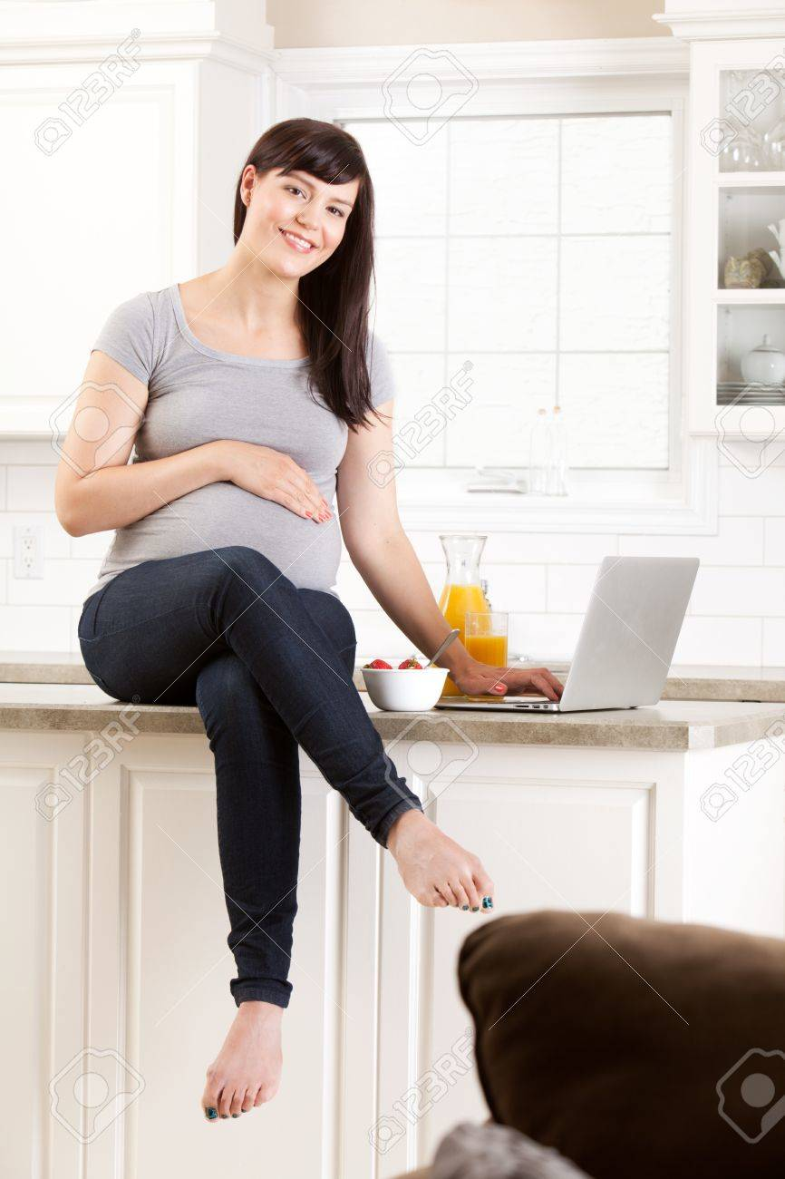 Healthy pregnant woman sitting on kitchen counter eating snack Stock Photo - 14943513
