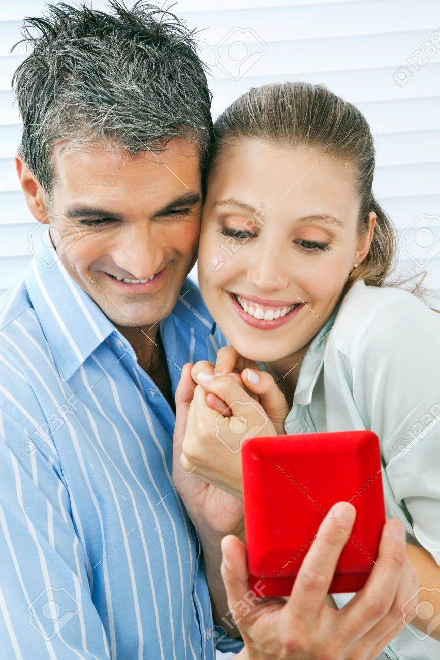 Middle aged man giving gift to happy woman holding a ring box Stock Photo - 14959069