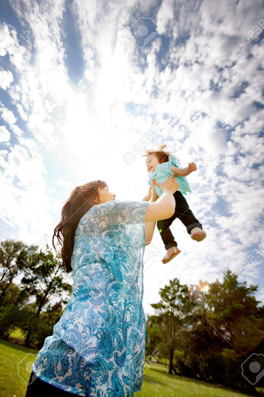Pregnant mother in third trimester throwing daughter up in the air Stock Photo - 15347751