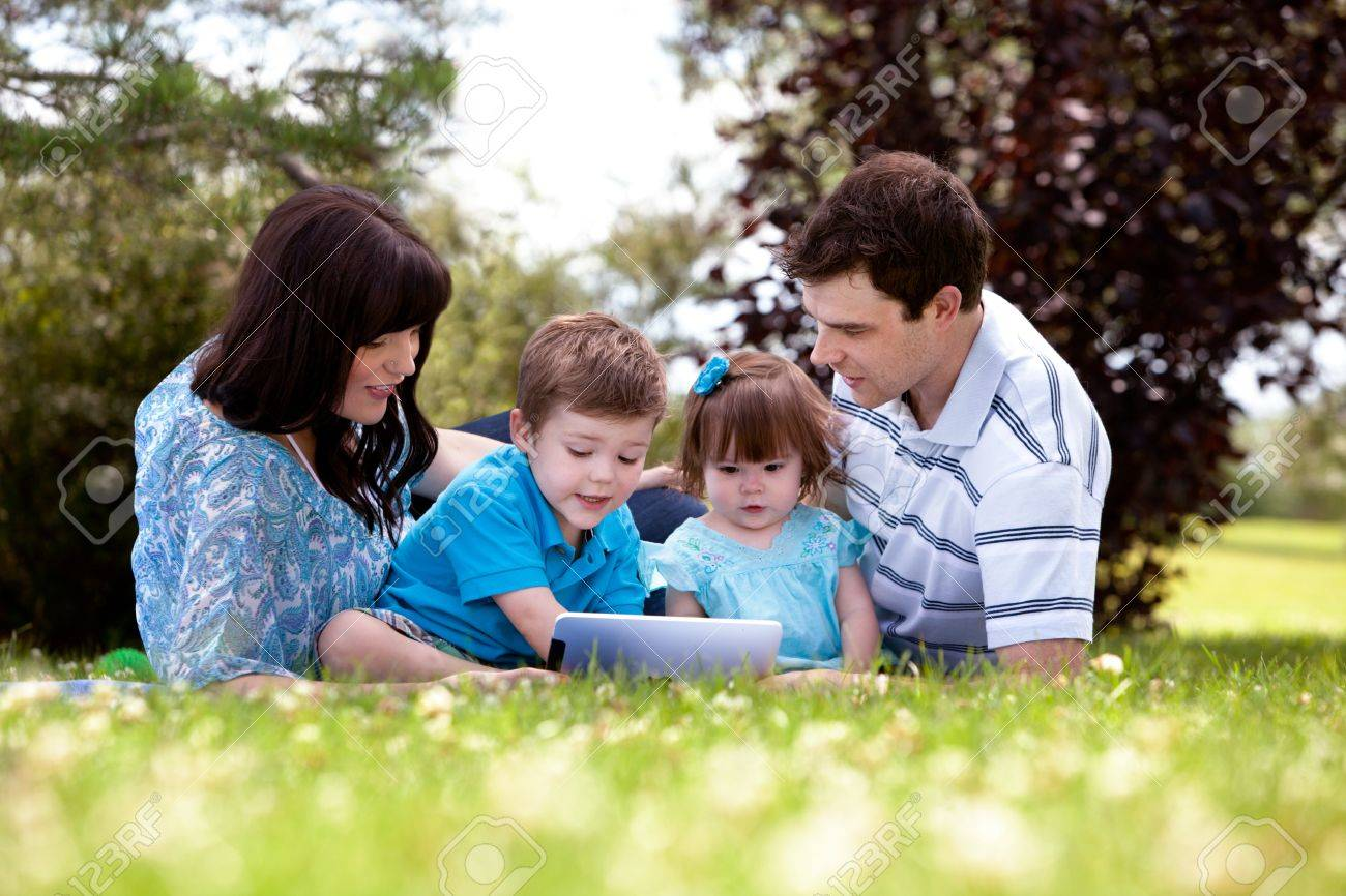 Happy family of four using a digital tablet outdoors Stock Photo - 15347768
