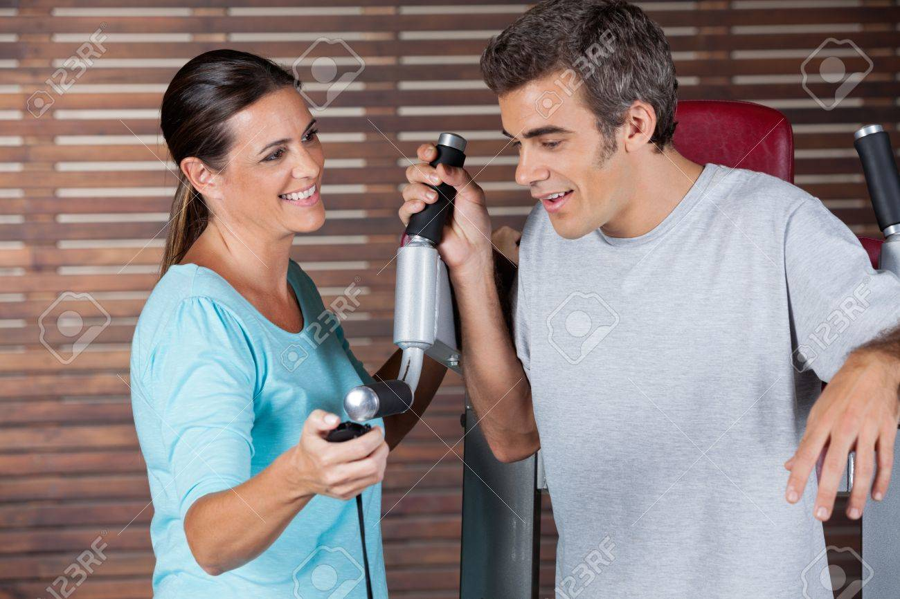 Mature female instructor assisting man in getting down from exercise machine in health club Stock Photo - 15314885