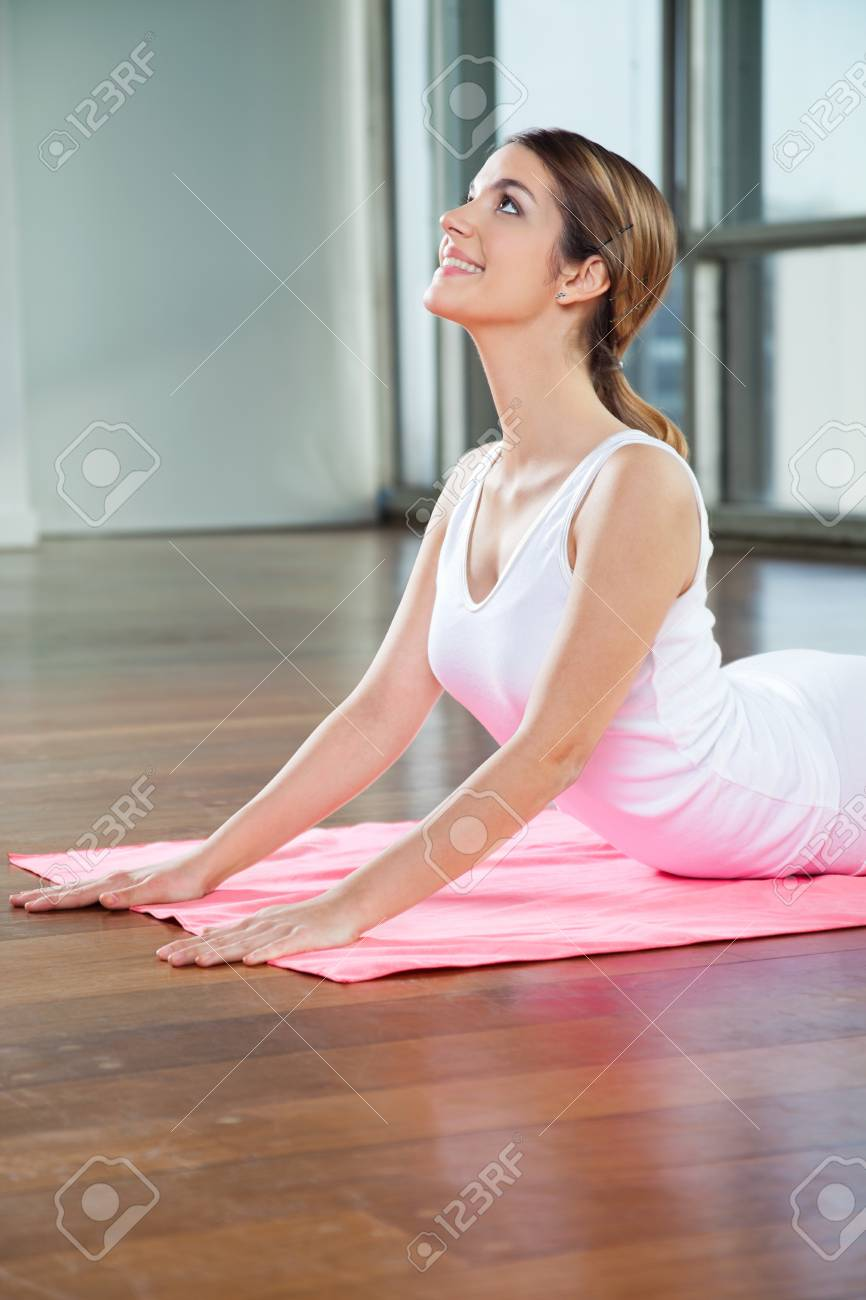 Happy young woman in a cobra pose on mat Stock Photo - 15316625