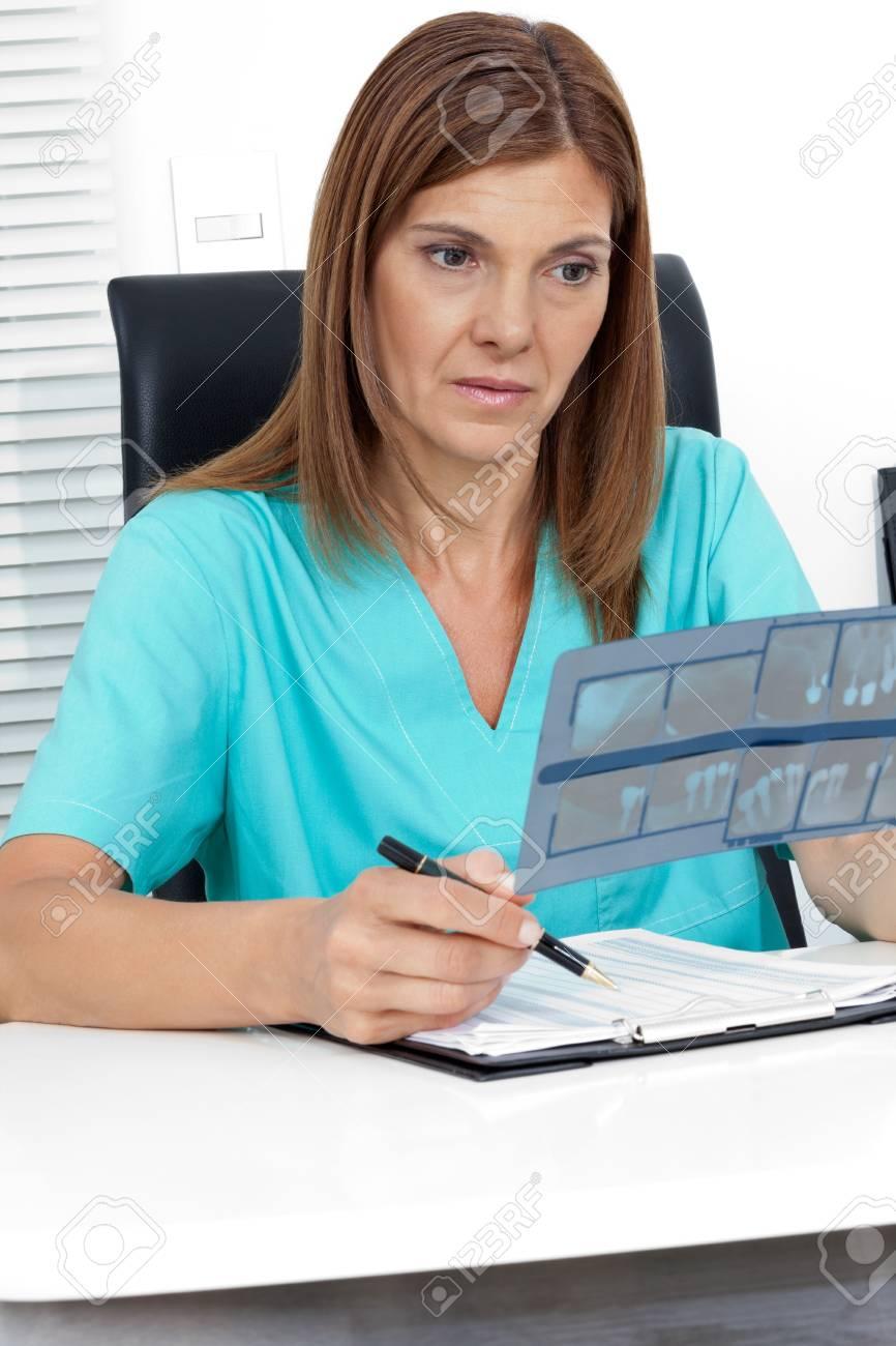 Female dentist analyzing dental X-ray report at office desk Stock Photo - 15353571