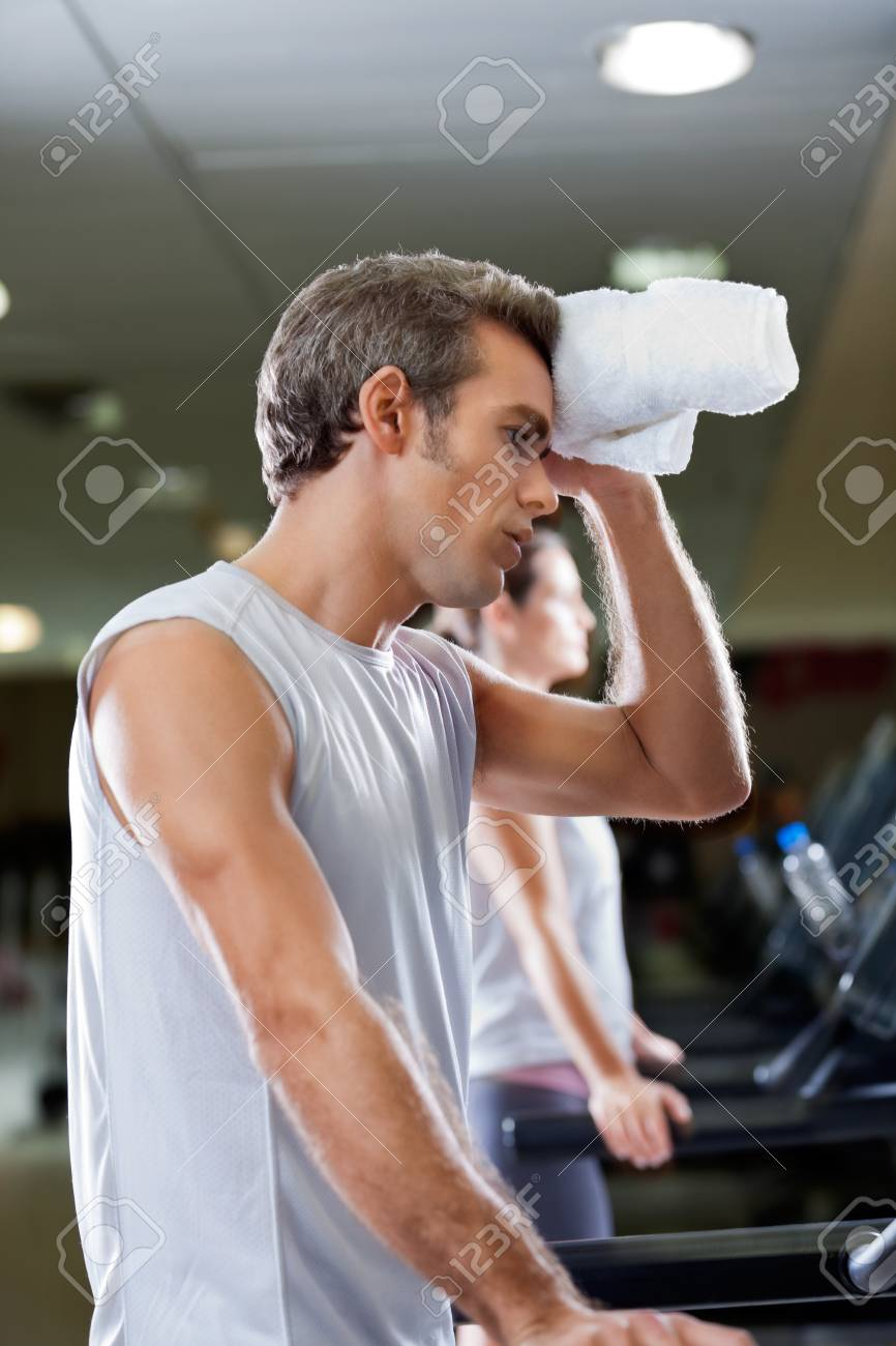 Side view of young man wiping sweat with towel at health club Stock Photo - 15450038