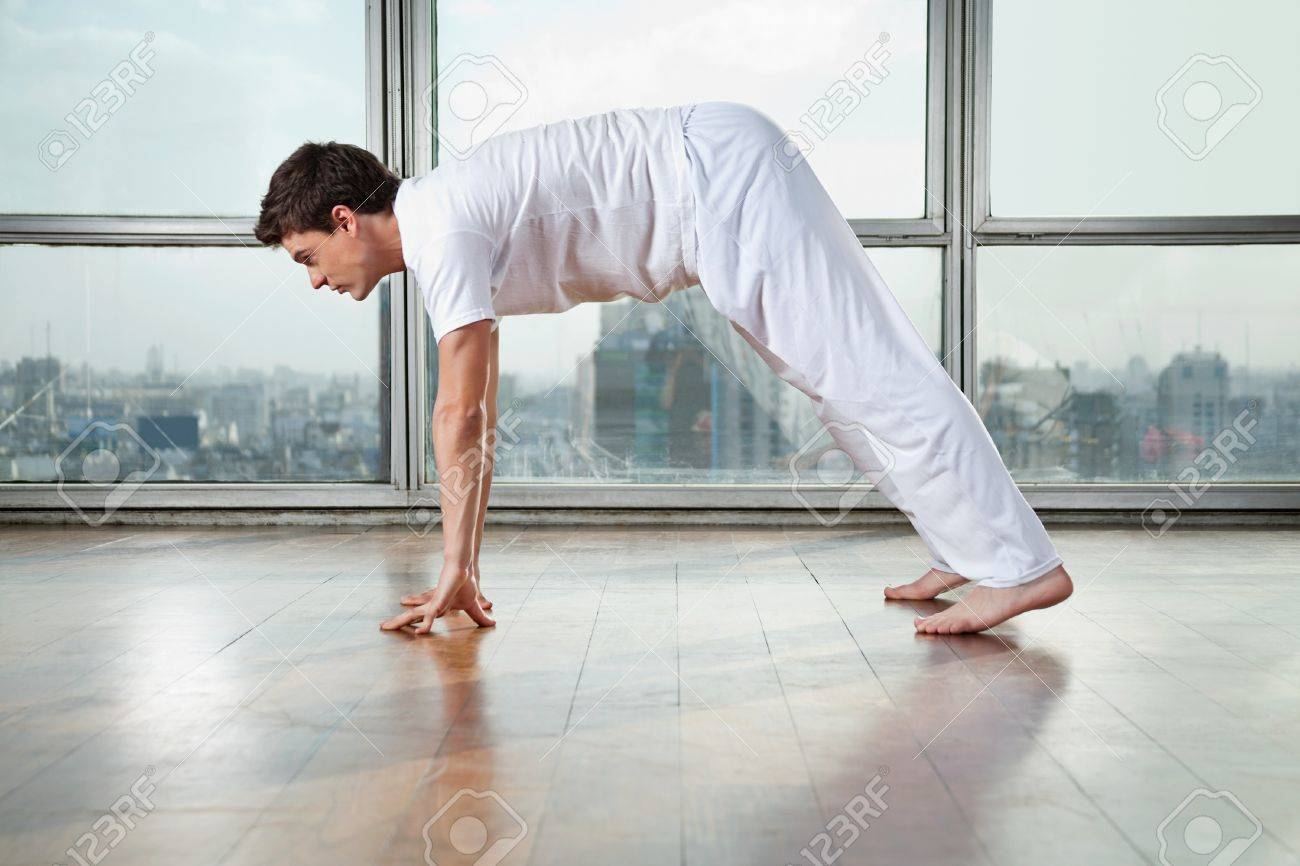 Side view of a young man practicing yoga called Downward Facing Dog at gym Stock Photo - 15449955