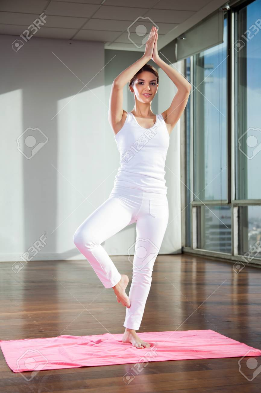 Full length of a young woman practicing yoga in Tree position on mat Stock Photo - 15450000