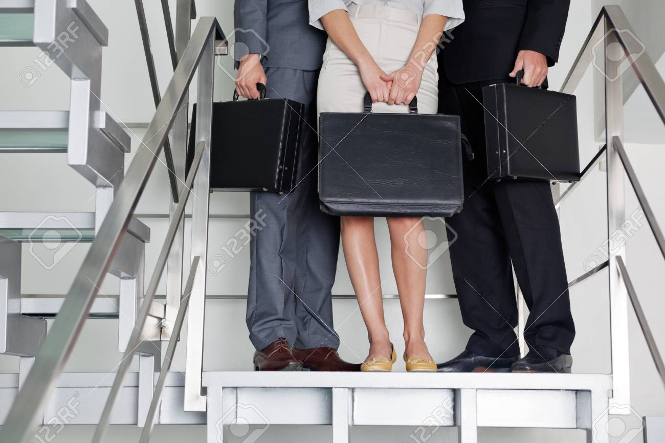 Low section of businesspeople with briefcases standing on steps at office Stock Photo - 16056559