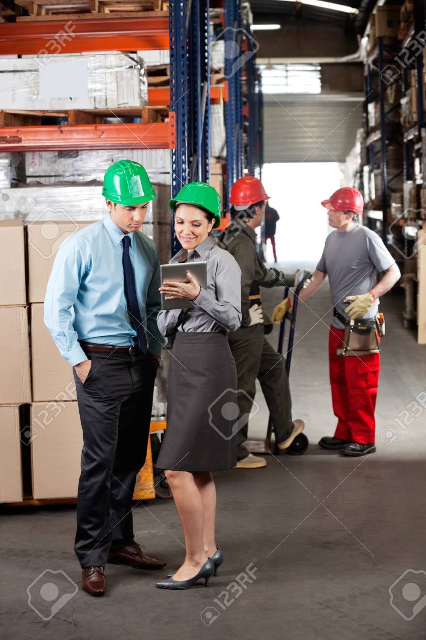 Female supervisor and male colleague using digital tablet with foremen communicating at warehouse Stock Photo - 16056639