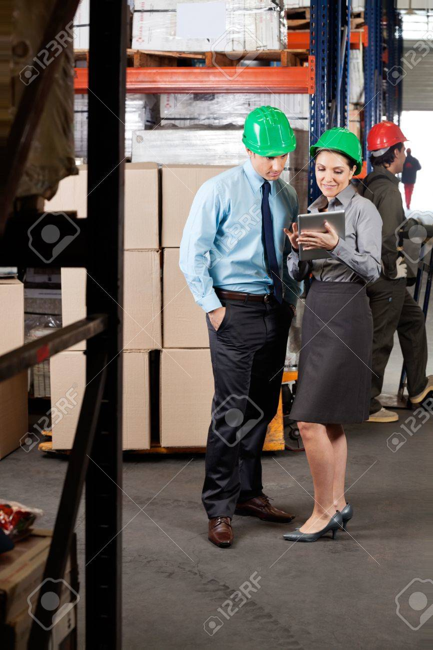 Young female supervisor and colleague using digital tablet at warehouse Stock Photo - 16056545