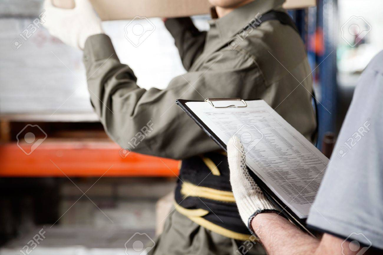 Midsection of foreman loading cardboard box with supervisor holding clipboard at warehouse Stock Photo - 16155457