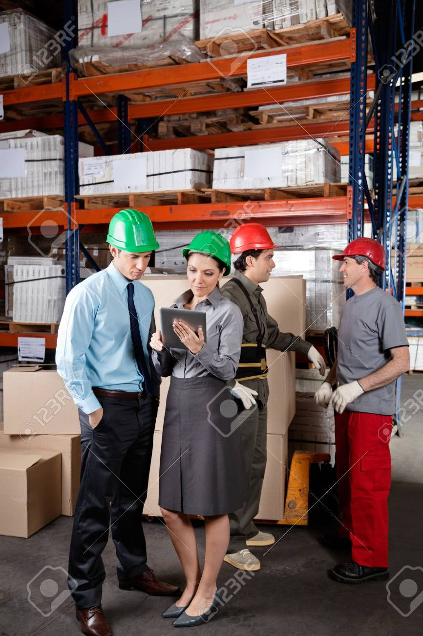 Supervisors using digital tablet with foremen discussing work at warehouse Stock Photo - 16155761