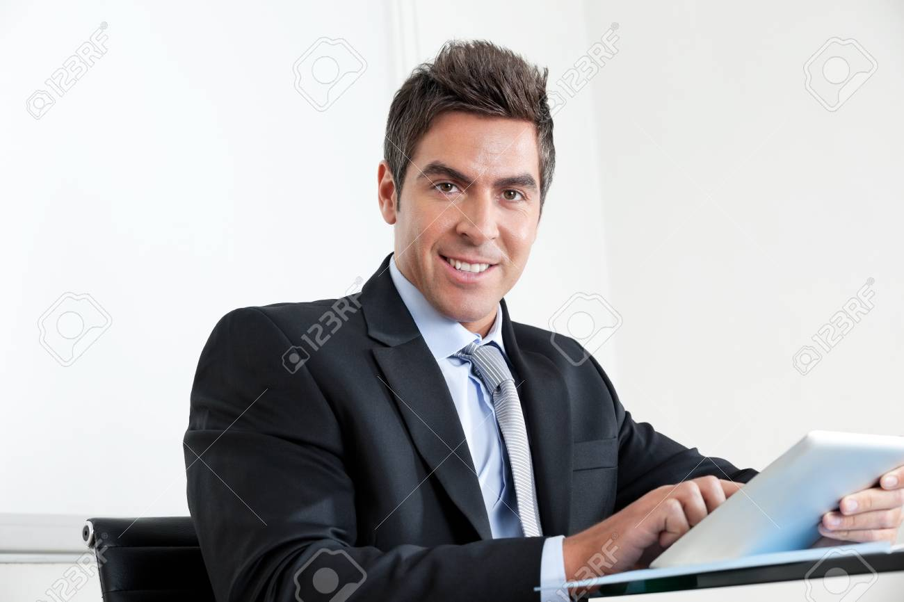 Portrait of handsome young businessman using digital tablet in office Stock Photo - 16191664
