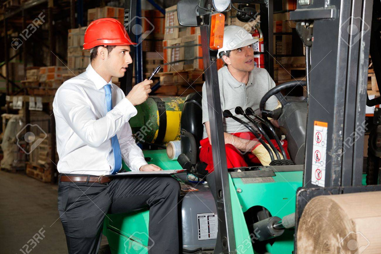 Male supervisor with clipboard instructing forklift driver at warehouse - 16191676
