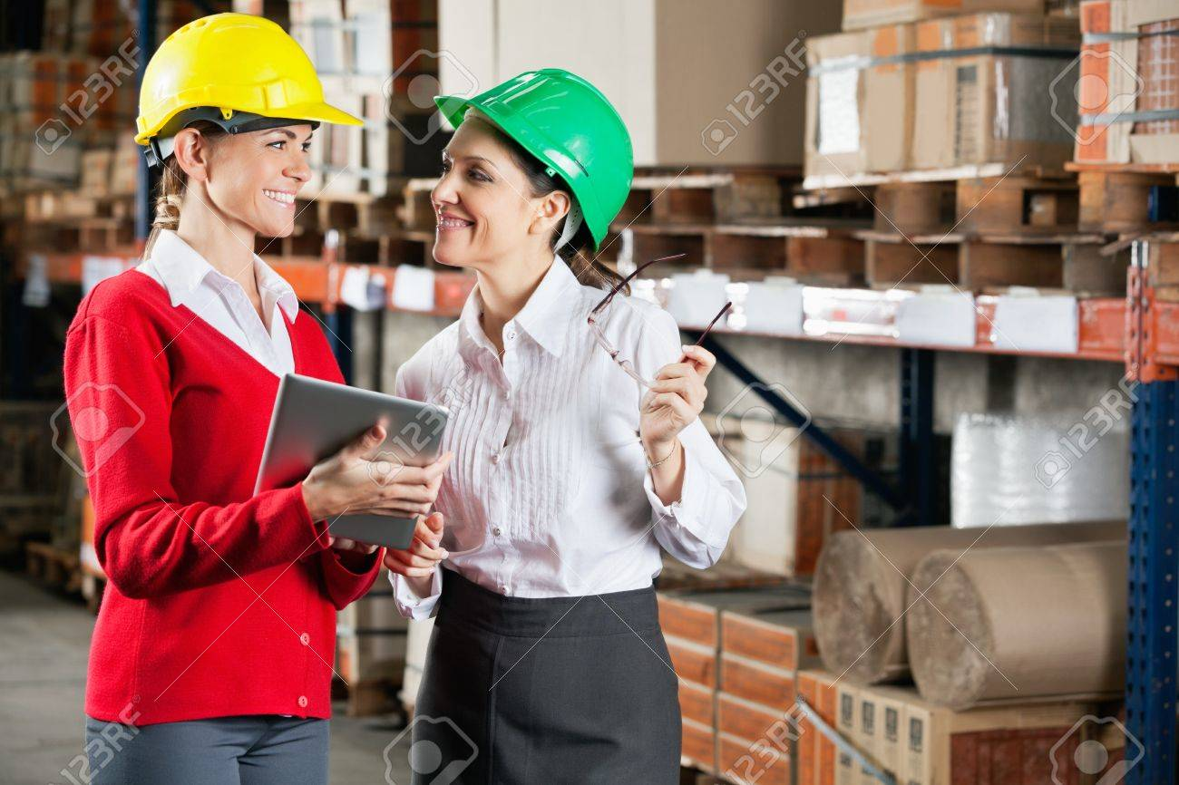 Two female supervisors with digital tablet discussing work at warehouse Stock Photo - 16191672