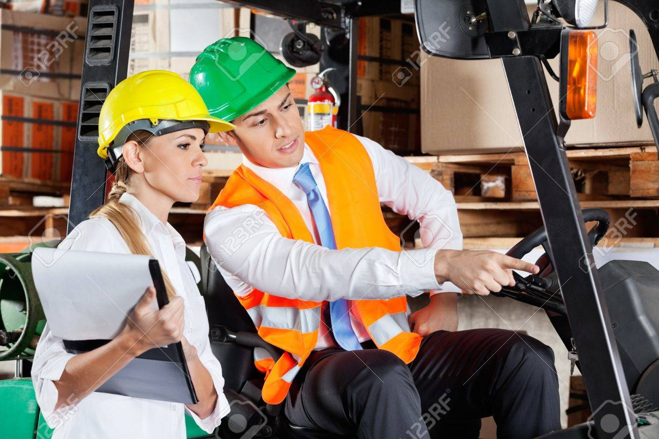 Male supervisor in forklift showing something to colleague with clipboard at warehouse Stock Photo - 16191696