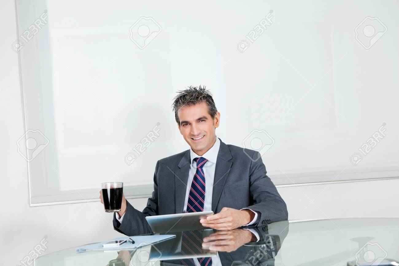 Businessman With Coffee Cup Using Digital Tablet In Office Stock Photo - 16470507