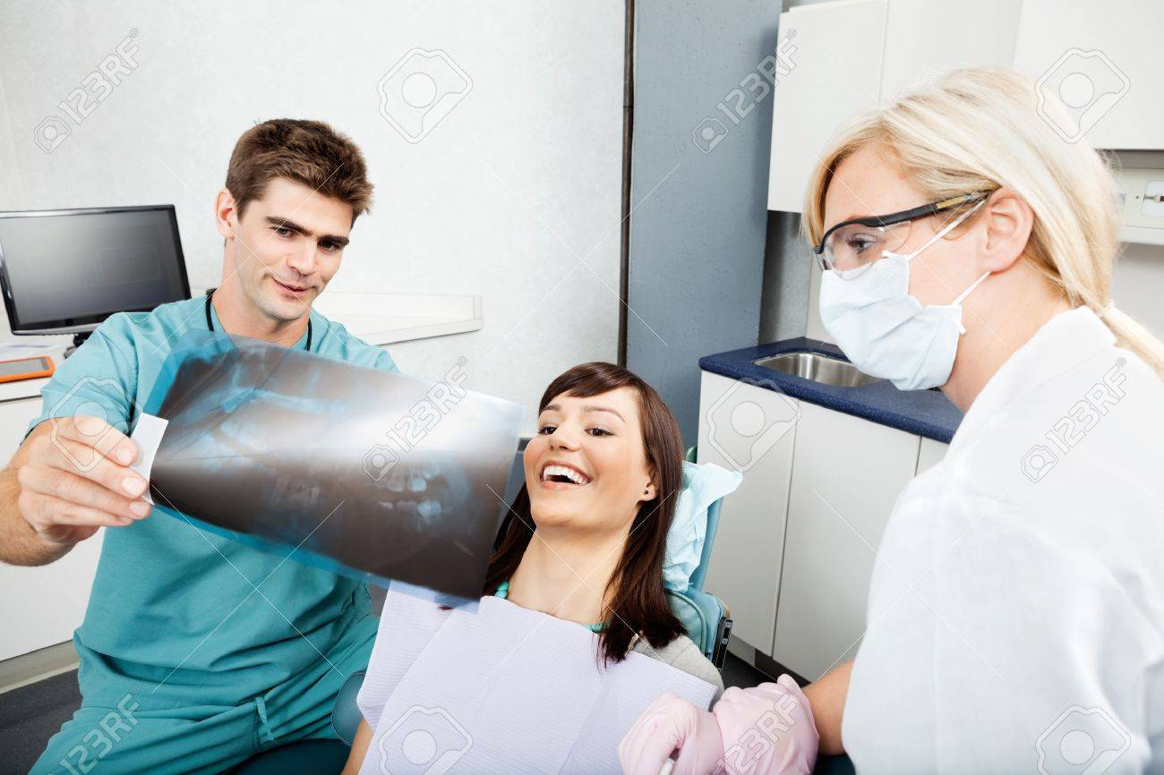 Dentist With Female Assistant Showing X-Ray Image To Patient Stock Photo - 16660944