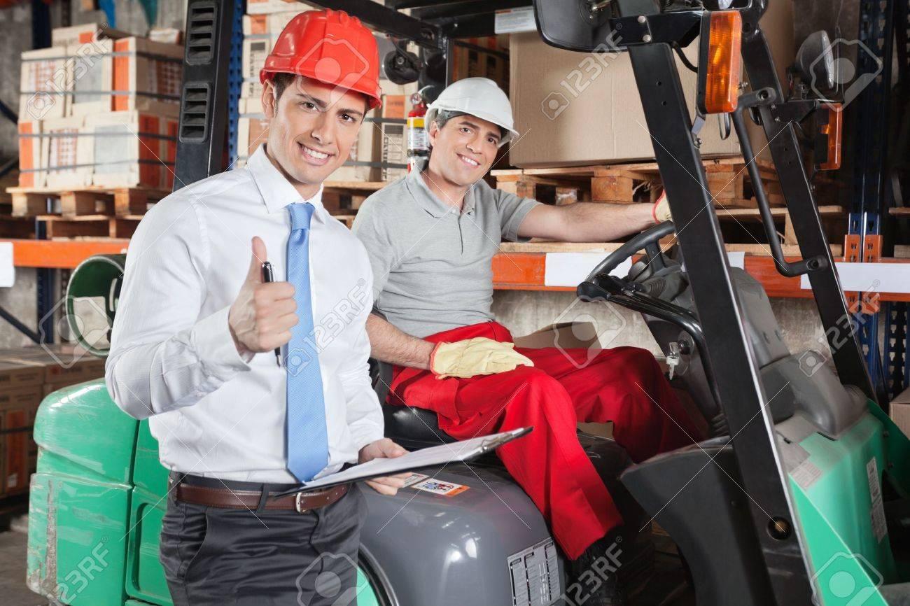 Supervisor Gesturing Thumbs Up At Warehouse Stock Photo - 16672704