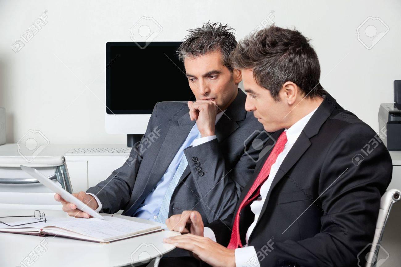 Thoughtful Businessmen Using Digital Tablet At Desk - 16672686