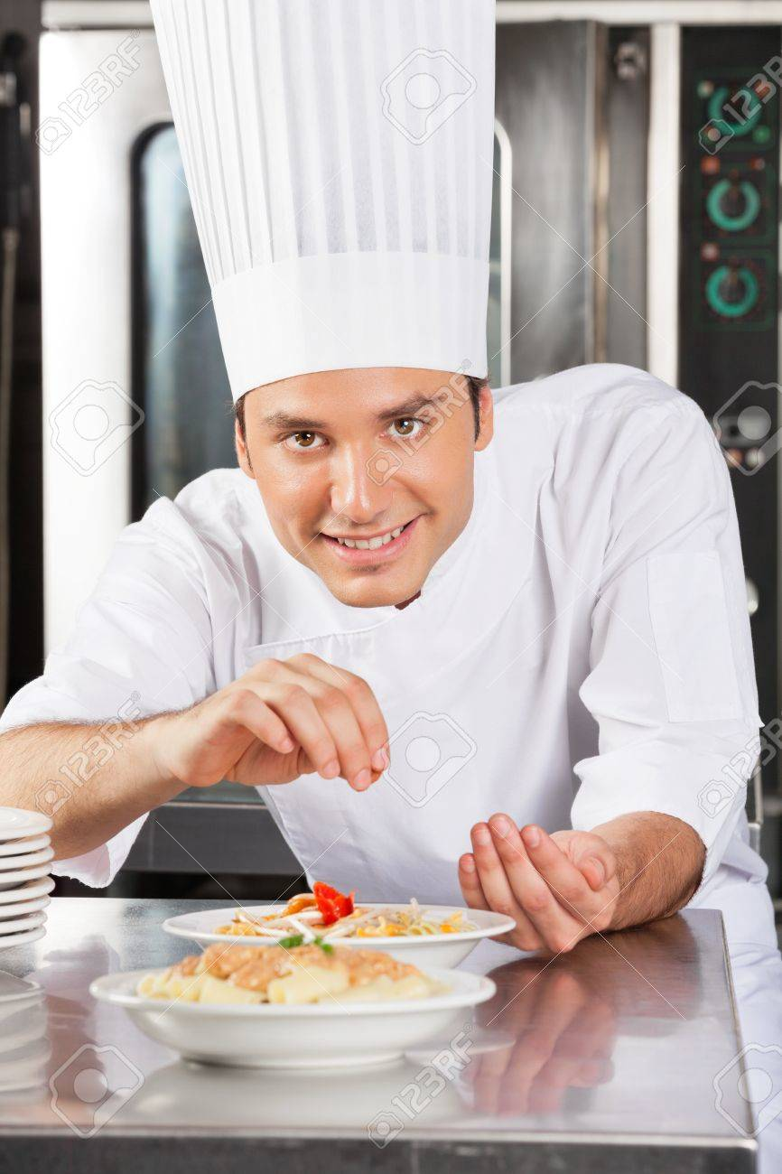 Happy Male Chef Sprinkling Spices On Dish Stock Photo - 18261562