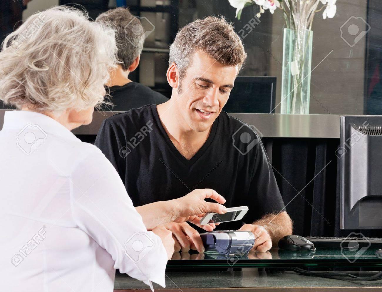 Customer Paying Through Mobile Phone At Salon Stock Photo - 18521621