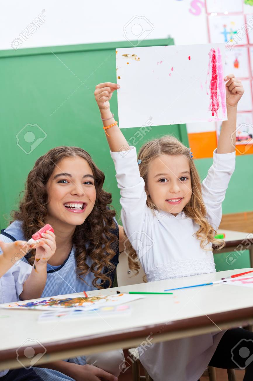 Teacher With Girl Showing Drawing At Desk Stock Photo - 19836618
