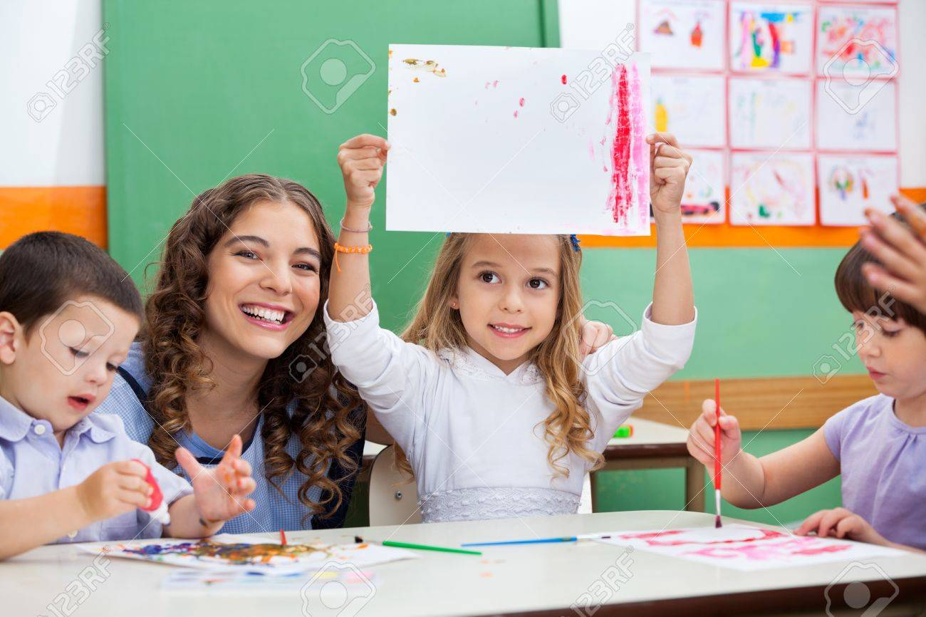 Teacher With Girl Showing Drawing At Desk Stock Photo - 19938057