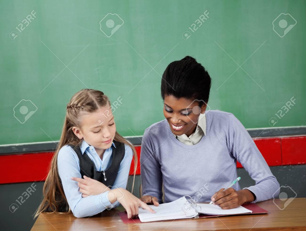 Schoolgirl Asking Question To Teacher At Desk Stock Photo 20198996