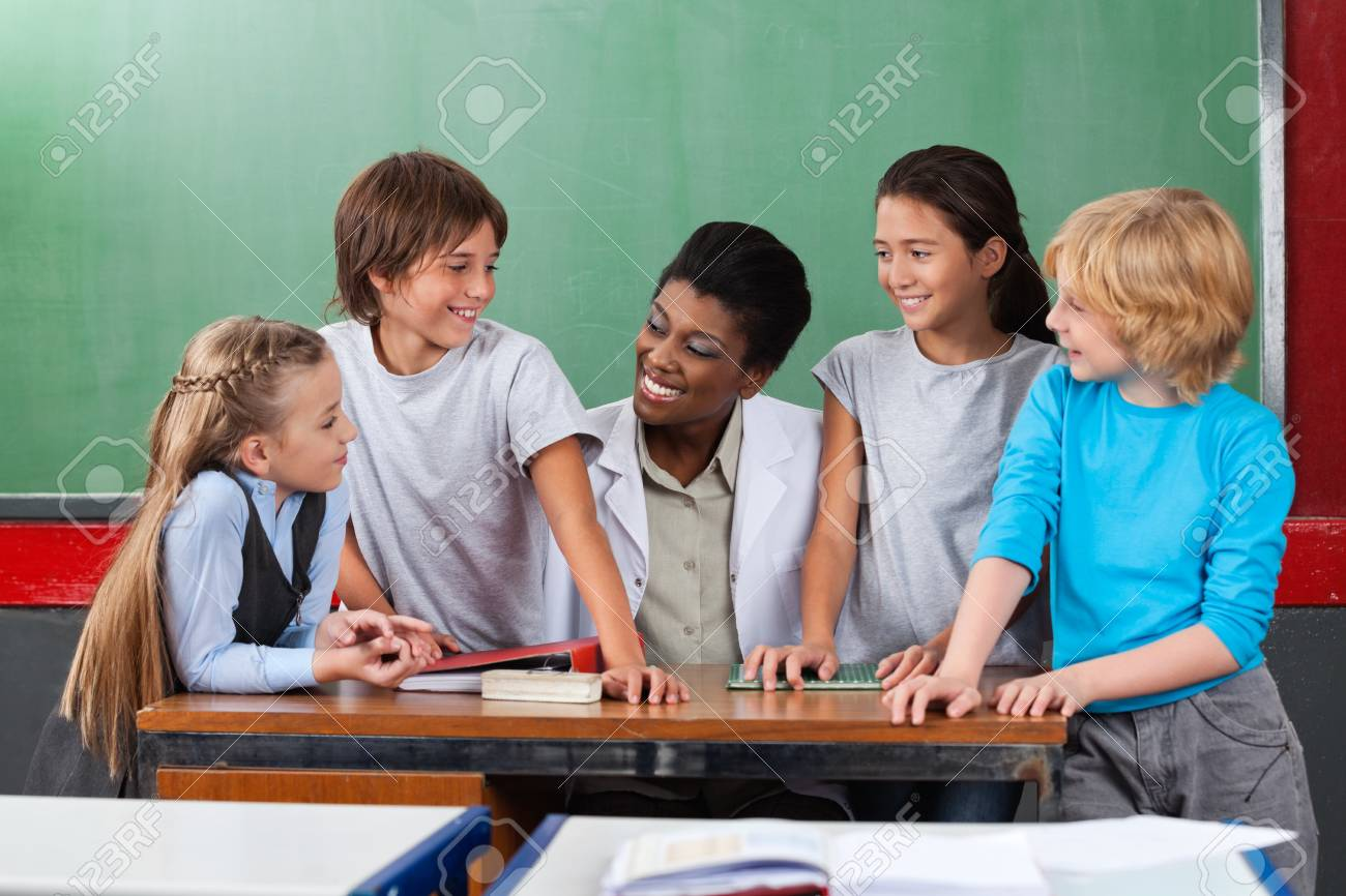 Happy Teacher With Students Communicating At Desk Stock Photo - 20591508