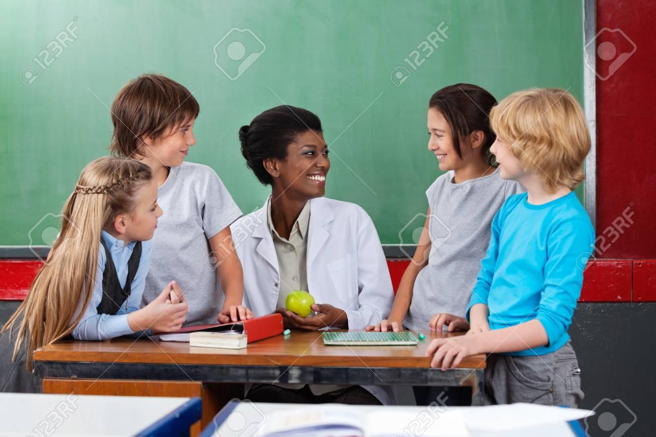 Schoolchildren Looking Teacher Sitting At Desk Stock Photo - 20633453