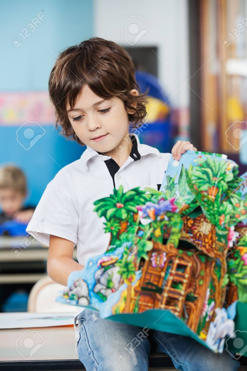 Boy With Popup Book Sitting On Desk In Kindergarten