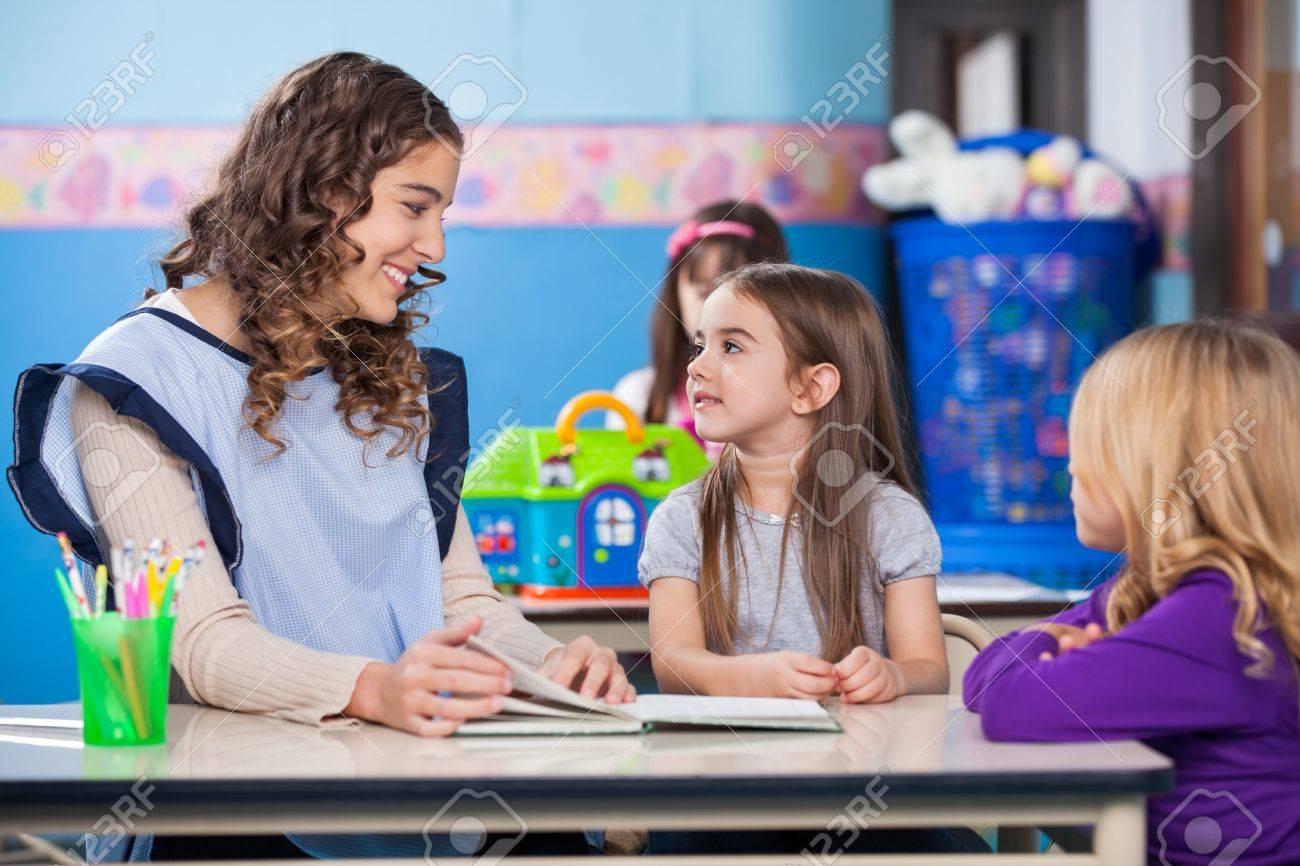Young Preschool Teacher Teaching Little Girls In Classroom Stock ...