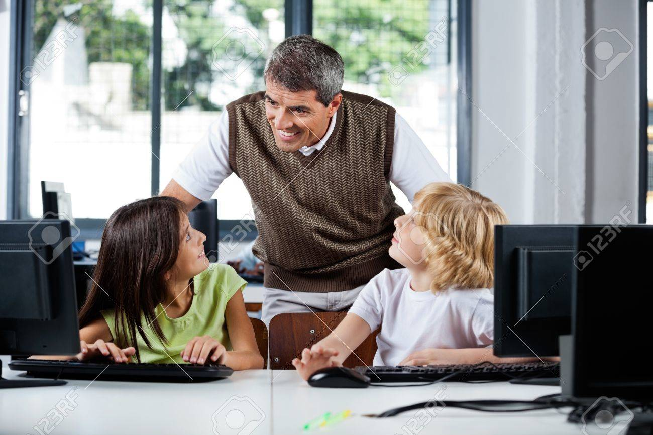 Happy mature male teacher assisting schoolchildren in using desktop PC at computer lab Stock Photo - 23745306