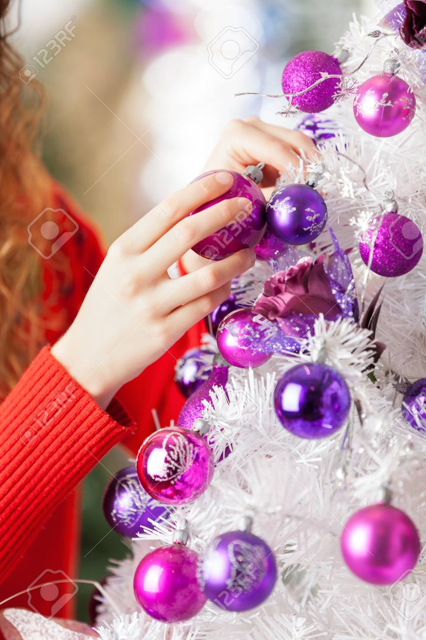 Cropped image of female owner hanging balls on Christmas tree at store Stock Photo - 23746380