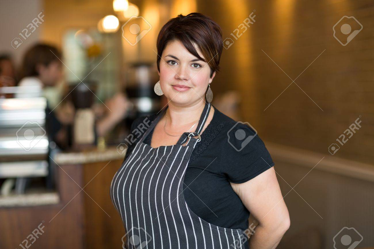 Portrait of confident young female owner smiling at cafeteria Stock Photo - 23764664