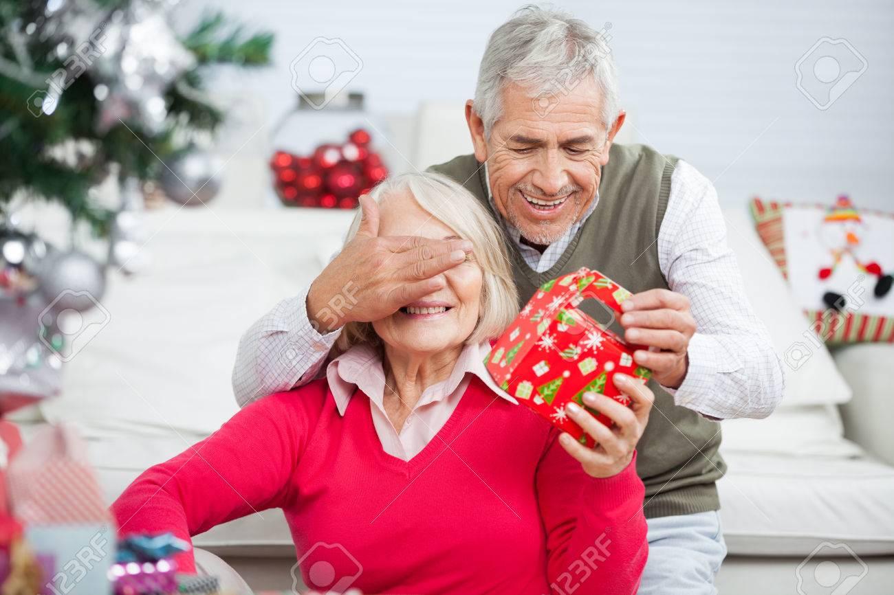 Happy Senior Mann Für Frau Augen Während Er Weihnachtsgeschenk Zu ...