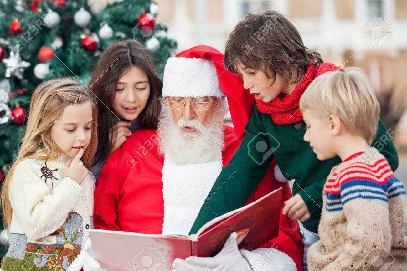 santa claus and children reading book against christmas tree stock photo 23726611 - Santa Claus Children