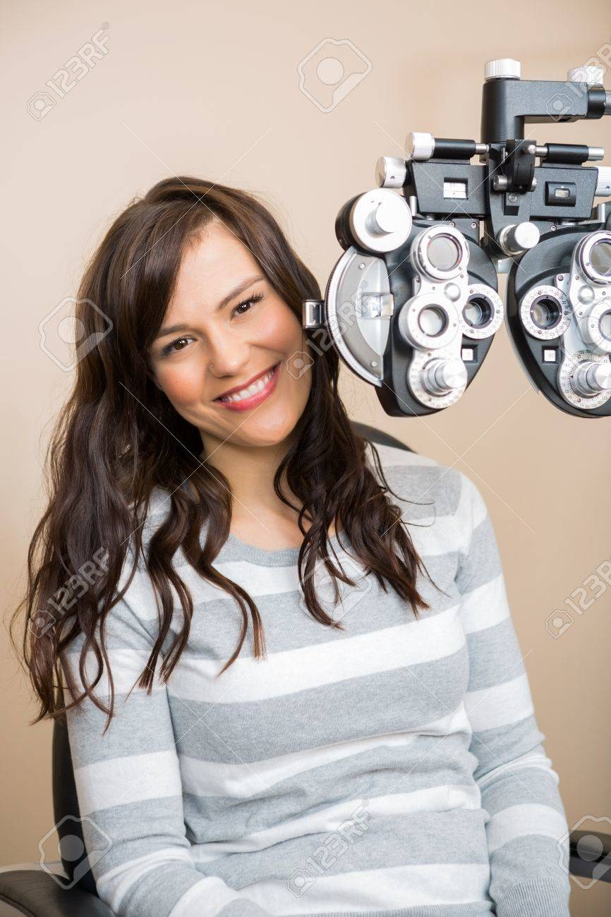 27bfdfd4b6b1 Portrait of beautiful young woman sitting behind phoropter during eye exam  Stock Photo - 23743335
