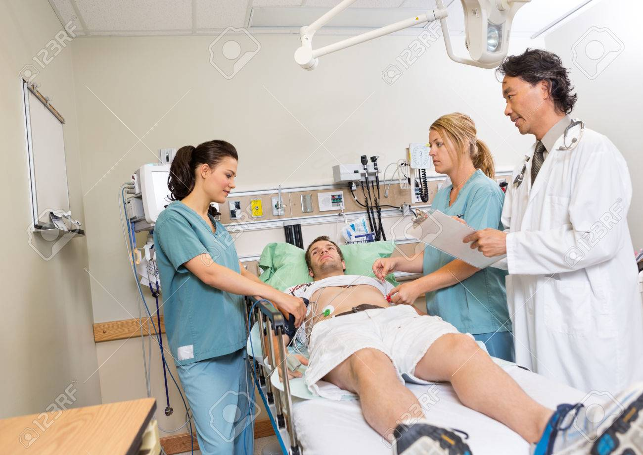 Multiethnic doctor and nurses checking patient in hospital - 23743497