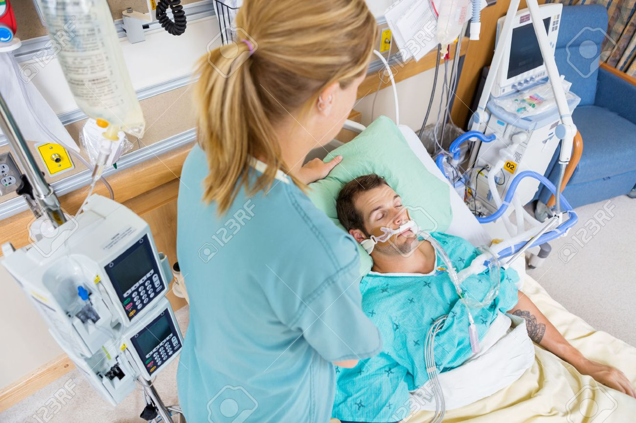 High angle view of nurse adjusting young patient's pillow in hospital room - 23743574
