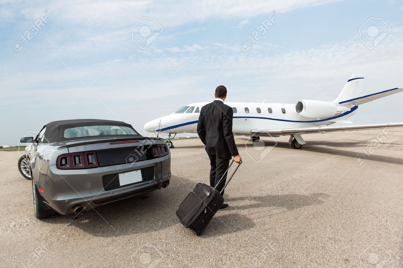 Businessman with luggage standing by car and private jet at airport terminal - 25295543